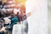 Ice sculpture carving man use electric chainsaw cut frozen winter